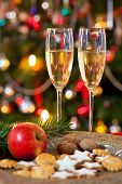 image of champagne color  - Christmas composition with two glasses of champagne standing on table behind a plate decorated with cookies and apple - JPG