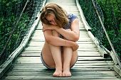 stock photo of saddening  - Portrait of pretty sad girl on the bridge - JPG