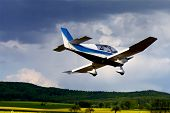 stock photo of glider  - a glider flying over a landscape in the sky - JPG