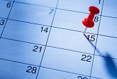 foto of reminder  - Red pin marking the 15th on a calendar as a reminder of an important event close up low angle view - JPG