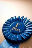 pic of rosettes  - Blue first place winner rosette or badge from pleated ribbon with central text to be awarded to the winner of a competition on a graduated beige background with copyspace - JPG