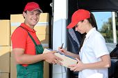 foto of moving van  - Smiling young man and woman postal delivery courier man before cargo van cargo delivery - JPG