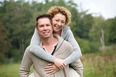 picture of piggyback ride  - Close up portrait of a smiling couple having fun with piggyback ride - JPG