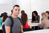 image of classmates  - Portrait of confident male college student carrying backpack with classmates in background