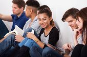 image of classmates  - Portrait of smiling female college student sitting with classmates against wall in classroom - JPG