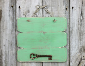 picture of skeleton key  - Blank green sign with bronze antique skeleton key hanging on weathered wood background - JPG