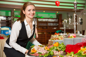 stock photo of buffet catering  - Catering service employee or waitress preparing a buffet - JPG