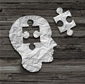 stock photo of wood pieces  - Puzzle head brain concept as a human face profile made from crumpled white paper with a jigsaw piece cut out on a rustic old wood background as a mental health symbol - JPG