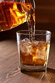 stock photo of whiskey  - whiskey and natural ice on old wooden table - JPG