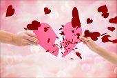 stock photo of girly  - Hands holding two halves of broken heart against digitally generated pink girly design - JPG
