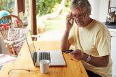 foto of card-making  - Mature Man Making On Line Purchase Using Credit Card - JPG