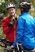 stock photo of bike path  - Two Mature Male Cyclists Riding Bikes Along Path - JPG