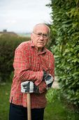 picture of spade  - Elderly man standing in garden wearing work clothes and holding spade worried face - JPG
