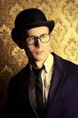 foto of bowler  - Portrait of a handsome young man in elegant suit and bowler hat posing over vintage background - JPG