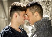 picture of cuddle  - young happy attractive gay men couple cuddling and kissing with forehead against each other outdoors on street in free homosexual love concept in urban background - JPG
