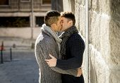 picture of homosexuality  - young happy attractive gay men couple holding hugging and kissing each other outdoors on street in free homosexual love concept in urban background - JPG