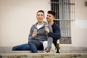 foto of cuddle  - young attractive Hispanic gay men couple cuddling celebrating together Valentines day or anniversary champagne toast on street smiling happy in love on urban background - JPG