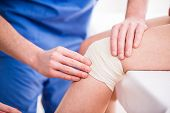 stock photo of bandage  - Doctor is rewinding knee bandage to young woman - JPG