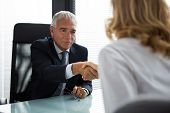 stock photo of 55-60 years old  - Two businesspeople male and female shaking hands during a meeting in the office - JPG