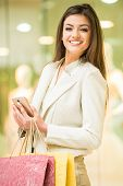 picture of shopping center  - Beauty woman with shopping bags in shopping mall with smartphone is looking at the camera - JPG