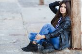 picture of straight jacket  - Beautiful young girl, Caucasian appearance, with dark, long, straight hair, brown eyes and beautiful dark eyebrows, wearing a striped shirt, blue jeans and black leather jacket, sitting on the street on the sidewalk