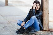 image of straight jacket  - Beautiful young girl, Caucasian appearance, with dark, long, straight hair, brown eyes and beautiful dark eyebrows, wearing a striped shirt, blue jeans and black leather jacket, sitting on the street on the sidewalk