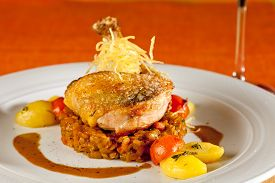 picture of guinea fowl  - Fried guinea fowl on red lentils with red and yellow cherry tomatoes and potatoes decorated with thyme and crispy potato straw - JPG