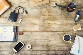 stock photo of touching  - Mix of office supplies and gadgets on a wooden desk background - JPG