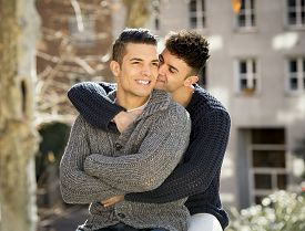 picture of homosexuality  - young happy attractive gay men couple cuddling and kissing outdoors on street in sexual freedom and free homosexual love concept in urban background - JPG
