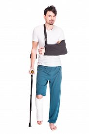 pic of crutch  - Full length view of a young man with broken leg and hand is using crutch isolated on white background - JPG