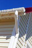 stock photo of gutter  - New plastic rain gutter system with drainpipe on white wall taken closeup - JPG