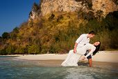 foto of barefoot  - groom holds bride in arms barefoot at edge of transparent water against cliffs - JPG