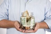 foto of retired  - Retired man holding his retirement piggy bank money account in his hands in a glass jar - JPG