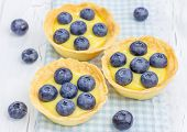 stock photo of curd  - Tartlets with lemon curd and blueberries closeup - JPG