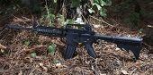 image of pine-needle  - Semi automatic rifle that is on some pine needles with trees nearby - JPG