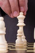 picture of chess pieces  - Businessman playing chess and holding queen chess piece - JPG