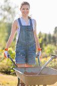 stock photo of wheelbarrow  - Portrait of happy female gardener pushing wheelbarrow at garden - JPG