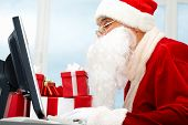 picture of merry christmas  - Portrait of Santa Claus in front of computer monitor - JPG