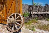 picture of wagon wheel  - old wooden wagon wheel near the open gate - JPG