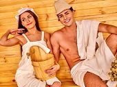 stock photo of sauna woman  - Couple man and woman  in hat  relaxing at sauna - JPG