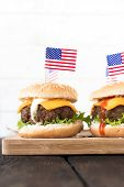 stock photo of beef-burger  - Mini beef burgers with American flag on wooden boardselective focus and blank space - JPG
