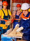 foto of millwright  - Group people  male builder with circular saw - JPG