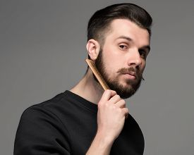 picture of moustache  - young man comb his beard and moustache on gray background - JPG