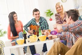 stock photo of social housing  - A small group of young people hang out at the house party chatting with each other while their friend having fun playing acoustic guitar - JPG