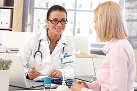 stock photo of stethoscope  - Happy female brunette doctor at medical office with patient - JPG
