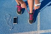 Runner woman tying running shoes laces getting ready for race on run track with smartphone and earph poster