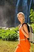 Tourist with backpack near waterfall poster