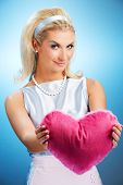 Beautiful young woman with fluffy heart pillow poster