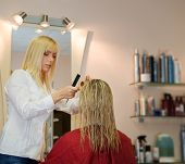 stock photo of hairspray  - Female hairdresser working in beauty salon - JPG