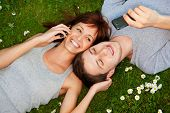 stock photo of mobile-phone  - Young couple with mobile phones outdoor - JPG